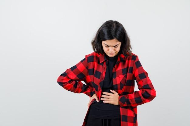 Teenie-mädchen leidet unter magenschmerzen im t-shirt, kariertem hemd und sieht schmerzhaft aus, vorderansicht.