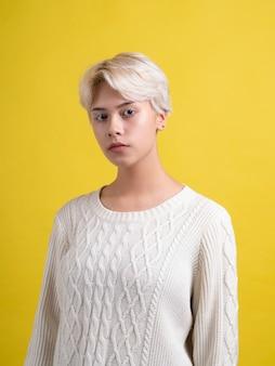 Teenie-mädchen mit kurzem weißen haarschnitt, der weißen strickpullover trägt