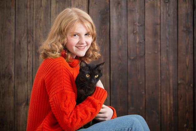 Teenie-mädchen mit schwarzer katze auf hölzernem hintergrund
