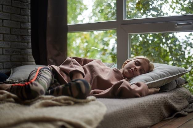 Teenie-mädchen schläft auf einem sofa am fenster