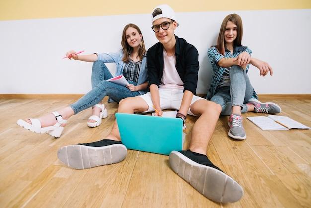 Teens mit laptop posiert im klassenzimmer