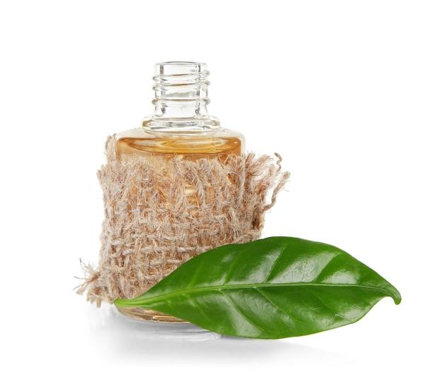 Teeöl in glasflasche mit frischen blättern, lokalisiert auf weiß