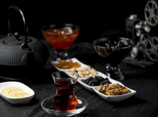 Teepause mit einem glas tee und genähten snacks, nüssen.