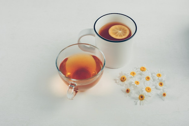 Tees und blumen in tassen. high angle view.