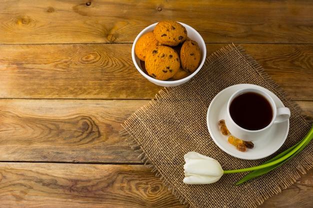 Teeschale und kekse auf sackleinen, draufsicht