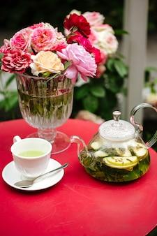 Teeservice im garten auf tisch mit blumen geschmückt