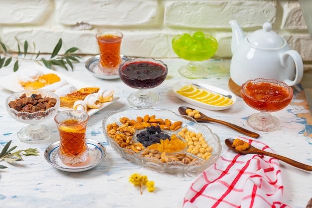 Teeservice mit verschiedenen traditionellen nüssen, zitronen, konfitüren und süßigkeiten auf weißer tischdecke