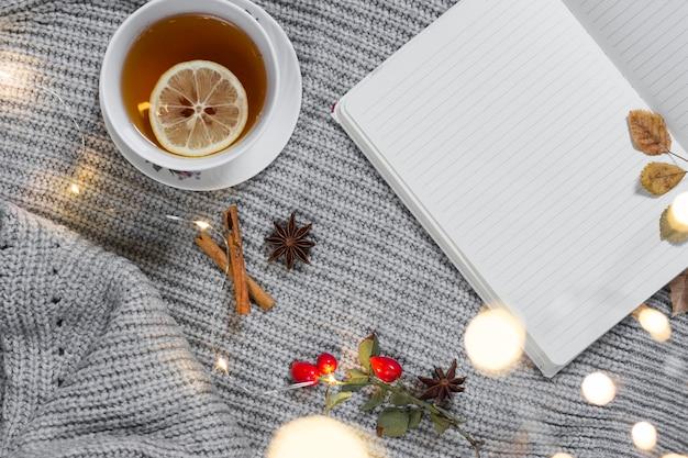 Teetasse auf gestricktem tuch mit notizblock