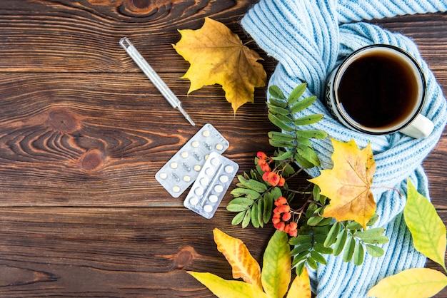 Teetasse mit thermometer, blauem schal und herbstlaub auf hölzernem hintergrund. grippesaison im herbst, krankheit.