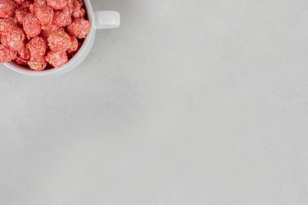 Teetasse überfüllt mit rotem, aromatisiertem popcorn auf marmortisch.