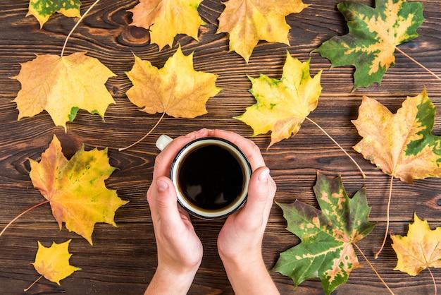 Teetasse und herbstlaub auf hölzernem hintergrund.
