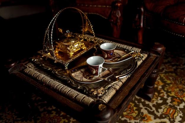 Teetasse und zuckerdose auf tablett stehen auf einem alten kleinen tisch. teeservice im vintage-stil. ein altes teeservice aus keramik und eine goldbox. konzept der teezeremonie. großer platz für beschriftung oder logo