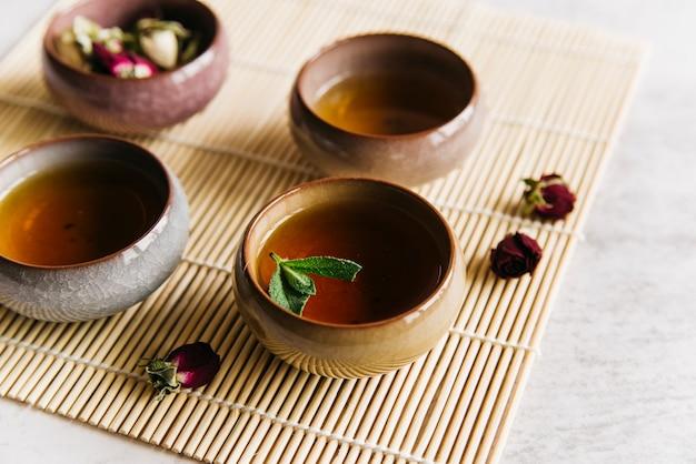 Teetassen mit minze und trockener rosafarbener blume auf tischset
