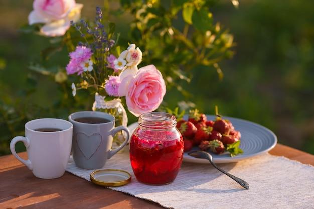 Teetassen mit rosa rosen auf einem holztisch am morgen