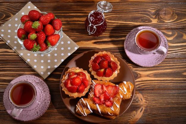 Teetrinken mit törtchen und kuchen mit erdbeeren