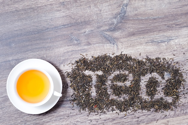 Teewort aus grünen teeblättern auf holzuntergrund
