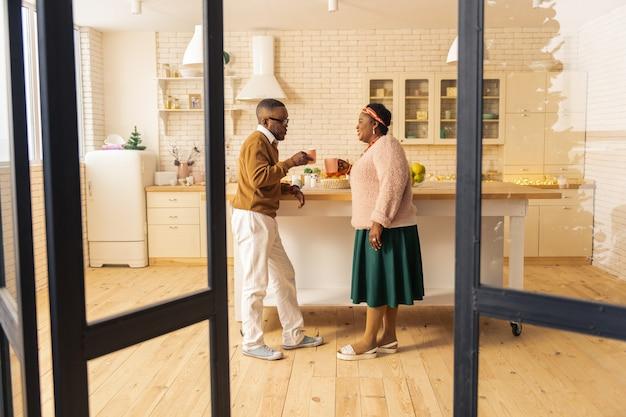 Teezeit. freudiges ehepaar, das beim gemeinsamen tee in der küche steht