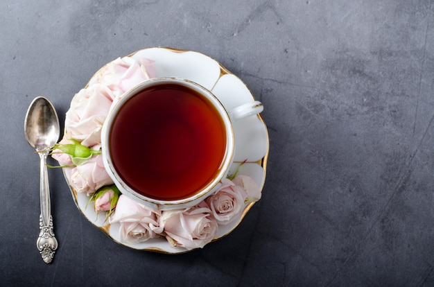 Teezeit hintergrund. top-down-stillleben mit vintage weißer porzellanteetasse mit sanften rosa rosen und schönem teelöffel auf einem dunkelgrauen hintergrund.