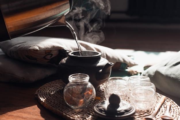 Teezeremonie am morgen drinnen bei sonnenaufgang, nahaufnahme. person, die heißes wasser in eine ton-teekanne gießt, selektiver fokus.