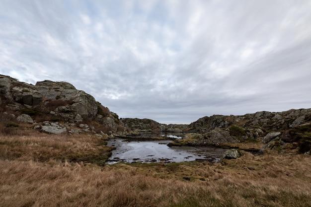 Teich durch den weg in der braunen küstenwinterlandschaft, am rovaer-archipel, rovaer-insel in haugesund, norwegen.