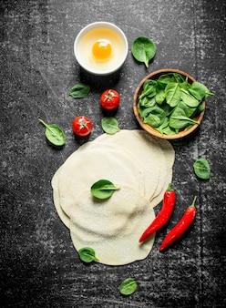 Teig für gedza-knödel mit spinat, tomaten, ei und chili auf dunklem rustikalem tisch