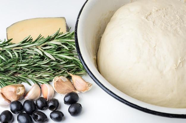 Teig für pizza in einer schüssel, rosmarin, oliven und käse auf einem weißen hintergrund