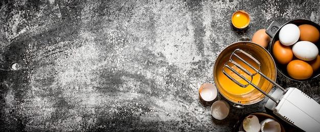 Teig hintergrund. zubereitung des teigs. frische eier im eimermischer verquirlen. auf rustikalem hintergrund.