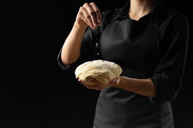 Teig in den händen des chefs des chefs mit mehl auf einem dunklen hintergrund.