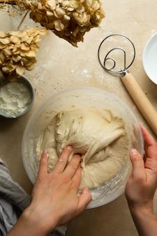 Teig kneten. hausgemachtes sauerteigbrot kochen. hände mischen brotteig in einer schüssel, ansicht von oben