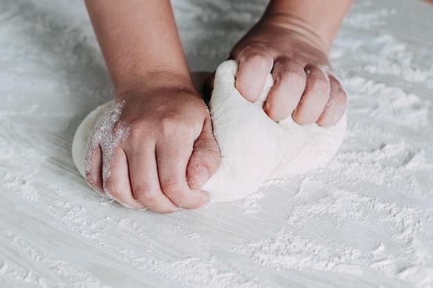 Teig machen durch weibliche hände auf weißem holztisch. weiblicher bäcker, der brotteig am weißen tisch vorbereitet.