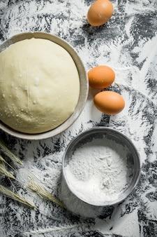 Teig mit eiern, ährchen und sieb. auf rustikalem hintergrund