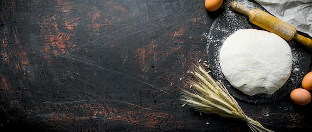 Teig mit eiern, nudelholz und ährchen. auf dunklem rustikalem hintergrund