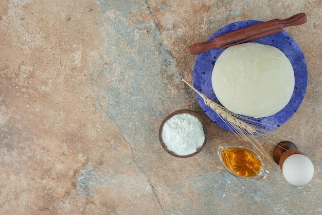 Teig mit nudelholz und ei auf marmortisch.