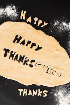 Teig mit thanksgiving inschrift und zwischen mehl