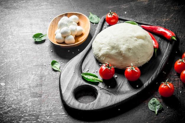 Teig mit tomaten, chili und mozzarella. auf dunkler rustikaler oberfläche