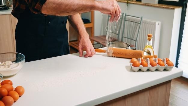 Teig von menschenhand zu hause in der küche mit weizenmehl herstellen. seniorenbäcker im ruhestand mit bone und schürze besprühen, sieben, verteilen von zutaten, die hausgemachte pizza und brot backen.