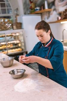 Teig vorbereiten. dunkelhaariger bäcker, der dem mehl ei hinzufügt, während er den teig für zukünftige croissants vorbereitet