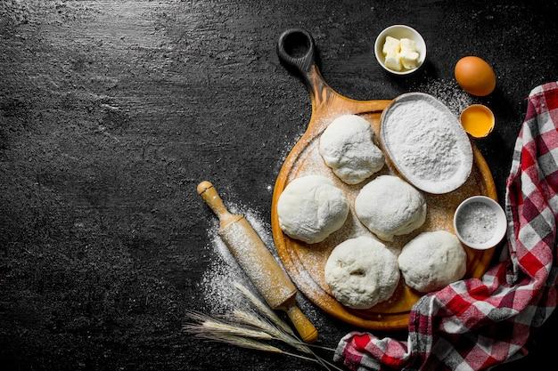 Teigoberfläche. teigstücke mit mehl, eiern und einer serviette. auf schwarzer rustikaler oberfläche