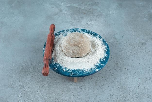 Teigrolle mit mehl auf holzplatte mit nudelholz.