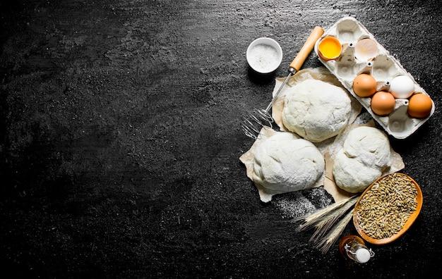 Teigstücke mit eiern, getreide und ährchen. auf rustikalem hintergrund