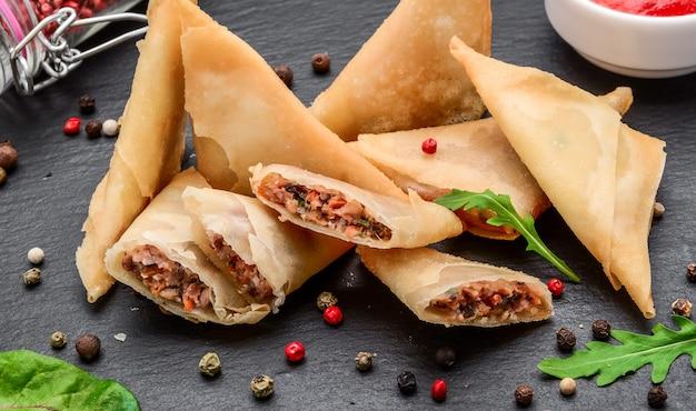 Teigumschläge mit belag und würziger sauce. asiatische küche