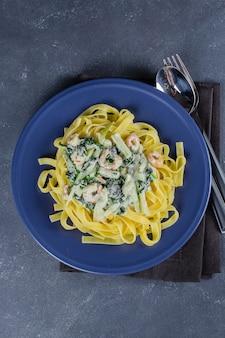 Teigwaren-bandnudeln mit spinat, garnelen und zucchini mit sahne auf blauer platte. italienisches essen