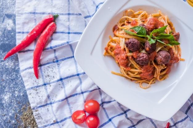 Teigwaren bolognese auf weißer platte. spaghetti auf blauem hintergrund
