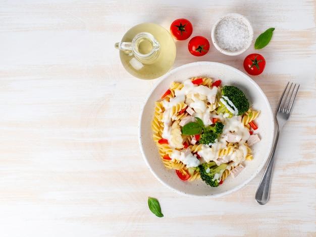 Teigwaren fusilli mit gemüse, fleisch, weiße soße auf weißem hölzernem