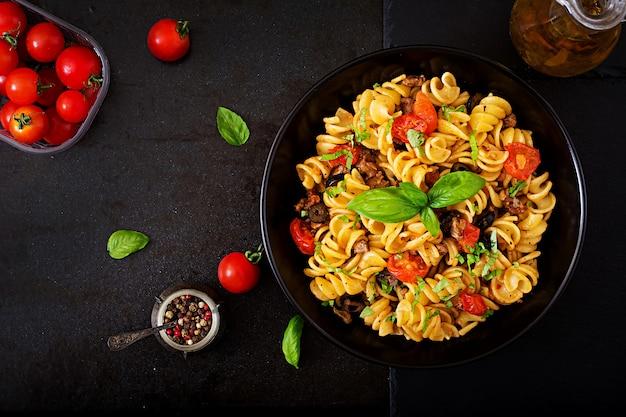 Teigwaren fusilli mit tomaten, rindfleisch und basilikum in der schwarzen schüssel auf tabelle. ansicht von oben. flach liegen