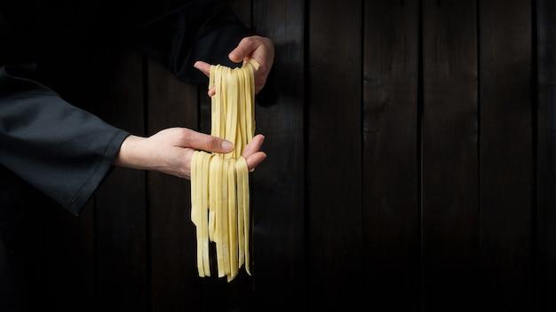 Teigwaren in den händen. hausgemachte pasta.