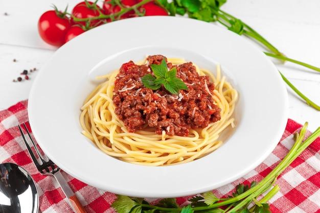 Teigwaren mit fleisch, tomatensauce und gemüse auf dem tisch