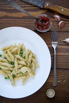 Teigwaren mit pestosoße, grünen erbsen, knoblauch und dill auf einer platte auf einem holztisch. in der nähe sind eine gabel, ein messer und getrocknete tomaten in einem glas. vegetarische küche. das konzept der gesunden ernährung