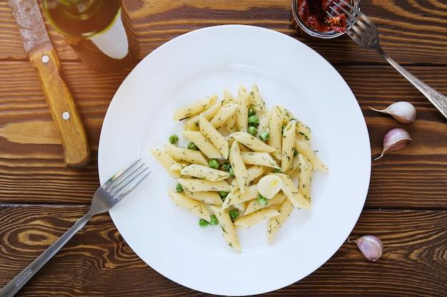 Teigwaren mit pestosoße, grünen erbsen, knoblauch und dill auf einer weißen platte auf einem holztisch. neben einer gabel und einem messer liegen sonnengetrocknete tomaten in einem glas. italienische küche. das konzept der gesunden ernährung.