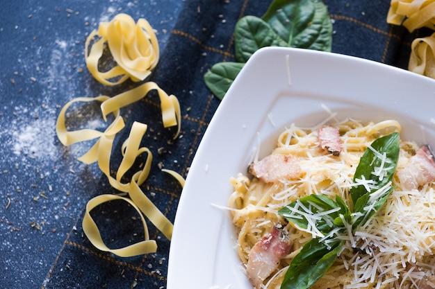Teigwaren mit speck, sahne, basilikum, parmesan, knoblauch, ei (eigelb) auf weißer platte